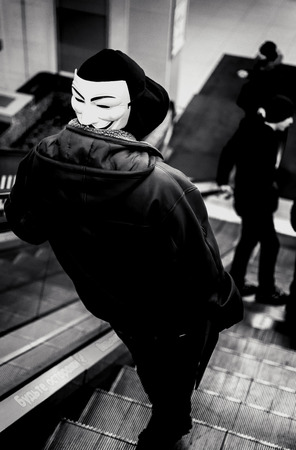 guy fawkes mask: UFA - RUSSIA 19TH DECEMBER 2015 - Young male wears a vendetta mask on the back of his head as he uses an escalator in a modern shopping centre