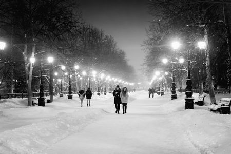 wintry weather: UFA - RUSSIA 22ND DECEMBER 2015 - People walk along an illuminated boulevard at night in the winter snow as ornate streetlamps shine in the night-time wintry weather