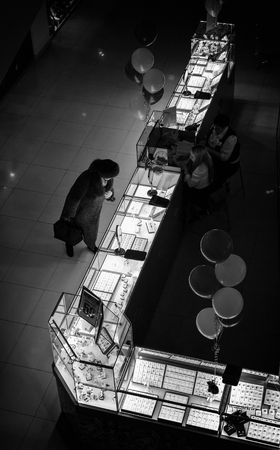 platinum: UFA - RUSSIA 19TH DECEMBER 2015 - Single elderly shopper in winter clothes looks down at the display of gold, silver, and platinum jewellery in a modern day shopping centre in Russia. Black and white image.