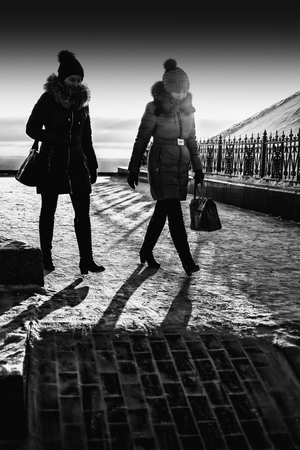 realism: UFA - RUSSIA 19TH DECEMBER 2015 - Two young women walking in the setting winter sun as the sun sets behind them casting shadows on the icy snow filled cobblestone brick pavement Editorial