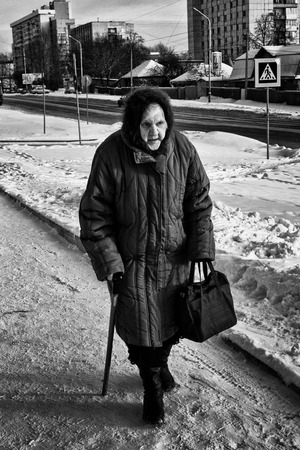 oap: UFA - RUSSIA 19TH DECEMBER 2015 - Single old woman walks along a path with the aid of her walking stick. The winter snow and ice cannot defeat her ability to travel and venture outdoors to visit friends and find the shops.