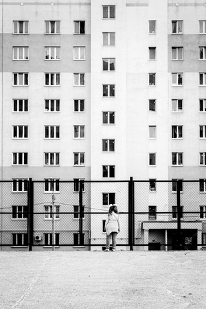 alienated: UFA - RUSSIA 22ND MAY 2014 - Young distant child looks at a through a wire fence at a large apartment block in a typical Russian setting