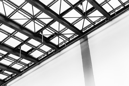 williams: Modern diagonal architectural abstract of a roofing structure and supports taken in black and white