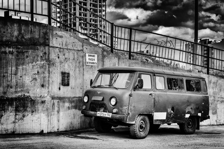 breadloaf: UFA - RUSSIA 22ND MAY 2014 - Old retro styles Russian UAZ vehicle parked in an urban landscape with a dramatic sky and oppressive concrete apartment blocks