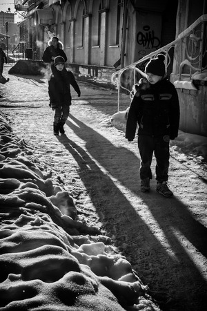 stretch out: UFA - RUSSIA 19TH DECEMBER 2015 - Two children walk along a winter sunlit path covered in snow, as one boy waits for his friend to play or jump on him. Their shadows stretch out before them. Editorial