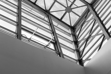 struts: Abstract style roofing detail interior of a modern building with glass panels in black and white