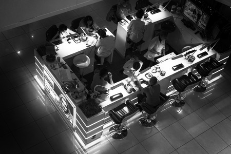 nail bar: UFA - RUSSIA 19TH DECEMBER 2015 - Modern nail bar taken from a high vantage point looking down at the women having their nails done at a local cosmetic beauty bar in Russia