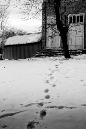 towards: Set of human footprints in the snow lead towards the comfort of a home in a winter setting