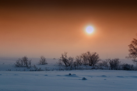 Setting sun with an orange cloudy sky settles over fresh fields of snow interspersed with bushes and trees in this winter style landscape image. Stock Photo