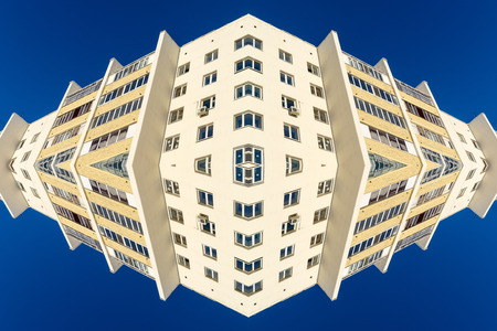 warped: Architecture abstract of a white apartment building block set against a bright blue summer sky. Copy space area with nobody in the scene. Symmetry creates repeating patterns. Stock Photo