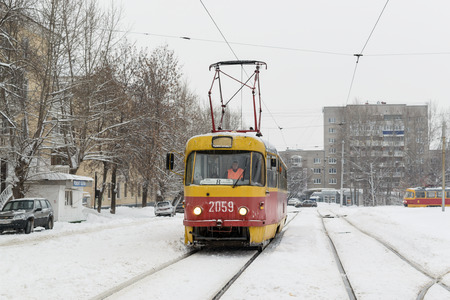 spite: UFA - RUSSIA 16TH JANUARY 2016 - Yellow public trolley bus tram continues to provide essential transport to people in spite of the cold winter weather in Ufa, Russia, in January 2016.