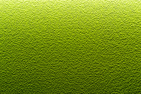 mottling: Green brightly lit surface with mottling and bumps from the plaster material. Copy space area for organic drink or alien effect background or backdrop.
