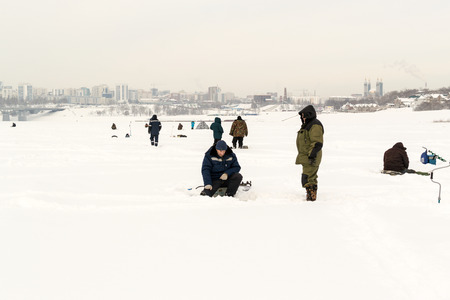 augers: UFA - RUSSIA 17TH JANUARY 2016 - Russian fishermen walk on the frozen White Belaya River to prepare for ice fishing using augers to drill though the frozen water in Ufa, Russia 2016.