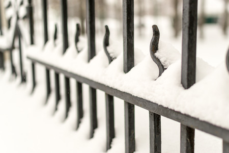 frost bound: Strong black cast iron fence with railings covered in fresh winter snow offering residents and homeowners protection.