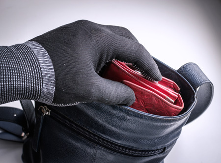 thievery: Burglar type thief wearing a black glove attempts to commit a crime by stealing a womans red leather purse from her unattended blue handbag Stock Photo