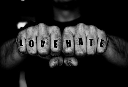 malandros: los puños cerrados de Thug con cicatrices con amor y el odio falsos tatuajes en los dedos. imagen de tonos con adición de grano para el estilo grunge amenazante diseños con área de espacio de la copia grande.