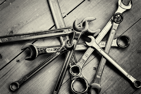 toolset: DIY Set of chrome metal home spanners. The wrenches are of various sizes with large copy space area for construction or repair concepts with nobody present. Tools set on a wooden work background. Monochrome image. Stock Photo