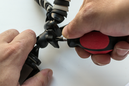 turn dial: Mans hand tightens a screw with a screwdriver to adjust a mini style tripod used for cameras or mobile smart phones.