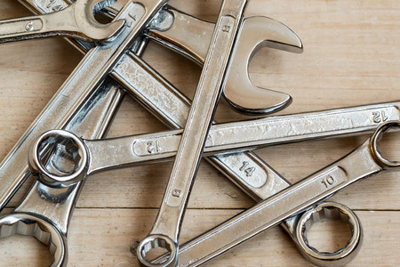 toolset: DIY Set of chrome metal home spanners. The wrenches are of various sizes with large copy space area for construction or repair concepts with nobody present. Tools set on a wooden work background.