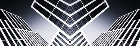 acute: Modern glass high-rise office building with acute angles showing reflections of a bright blue clear sky in Monochrome. Toned black and white wall art using symmetry.