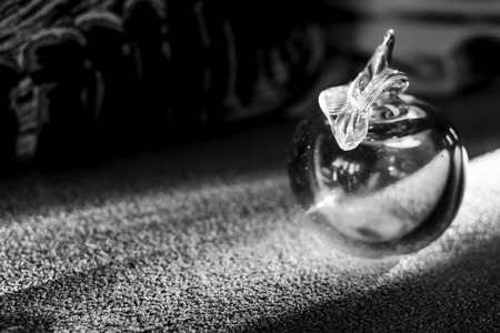 studio photograph: Monochrome art image of a glass apple ornament catching the sun rays. Natural studio photograph. Stock Photo