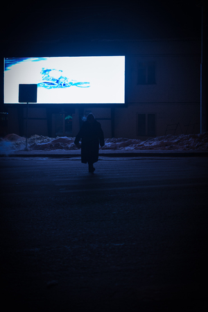 oap: UFA - RUSSIA 13TH FEBRUARY 2016 - Elderly woman safely crosses a street at night using the illumination from an advertising television advert to light her path in Ufa, Russia in 2016.