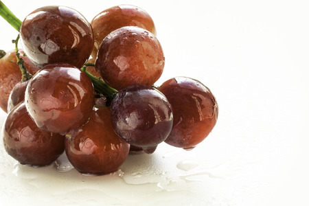 white grape: Bunch of red grapes in studio close-up with a mist of fresh water drops on a white background. Copy space area for menus or restaurant themed designs Stock Photo