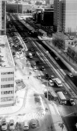 hectic life: City cars move down a street in a city. Aerial view from above in monochrome.