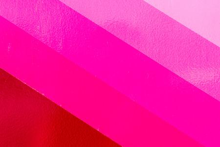 varying: Varying shades of a pink color paint that covers a textured wall. Copy space diagonal areas with rough textures. Stock Photo