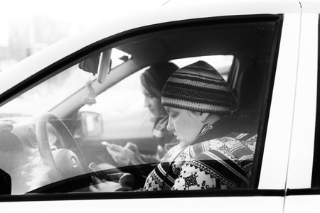 oblivious: UFA - RUSSIA 13TH FEBRUARY 2016 - Modern couple sit in a stationary car using their mobile phones oblivious to the world around them as they become transfixed by the use of their smartphones in Ufa, Russia in February 2016.