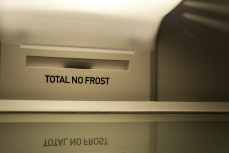 Fridge interior with total no frost in the inside. Close up with empty shelves and a refrigerator light on.