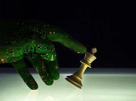 Computer artificial intelligence hand concept of check mate against a white king chess piece. AI technology brain of a robot arm supersedes human power. Copyspace area.