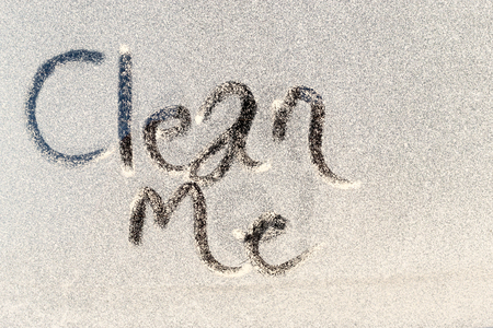etched: Clean Me text etched into the dirty grubby window of a window