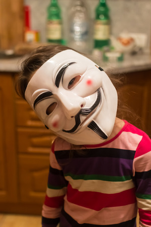 guy fawkes mask: UFA - RUSSIA 21ST FEBRUARY 2016 - Young girl looks at the camera whilst wearing a Guy Fawkes V for Vendetta mask in Ufa, Russia in 2016 usually worn by protestors