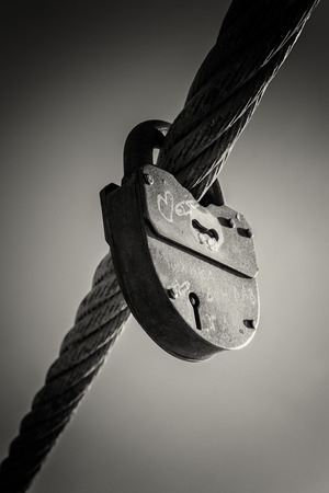 metal monochrome: Old industrial padlock attached to a metal cable. Black and white image in monochrome.