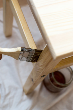 clothed: Casual clothed young woman uses a paintbrush to paint with varnish a pine chair or table surface.