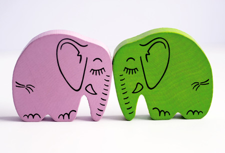 facing each other: Pink and green wooden elephants touching heads and kissing by facing each other. White background with copyspace area. Stock Photo