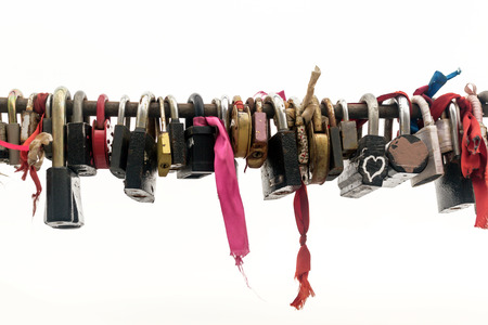 Line of various old rusting metal padlocks in different shapes locked and secured. White background sky area with copy space for eternal love and symbolic concepts or ideas of romance. Colour image.