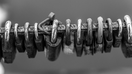 metal monochrome: Line of old rusting metal padlocks locked and secured. White background sky area with copy space for love as eternity, and symbolic concepts or ideas of romance. Monochrome black and white image. Widescreen stretched image.