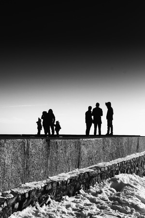 adds: Groups of people stand on the edge of the horizon in a monochrome black and white abstract. Clear sky overhead adds to the sense of surrealism of the image.