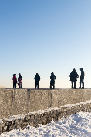 adds: Groups of people stand on the edge of the horizon in a colour abstract image of men and women in a unique environment. Clear sky overhead adds to the sense of surrealism of the image.