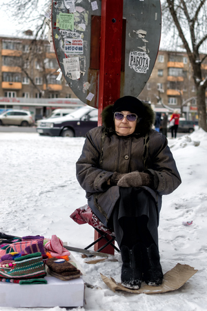 warmer: UFA - RUSSIA 1ST MARCH 2016 - An elderly woman sits on a folding seat with a cardboard foot warmer and sells home spun woolen socks and gloves in Ufa, Russia in the late winter of March 2016.