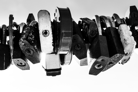 metal monochrome: Line of old rusting metal padlocks locked and secured. White background sky area with copy space for love as eternity, and symbolic concepts or ideas of romance. Monochrome black and white image.