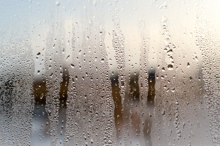Condensation forms water droplets on the surface of a clear glass house interior window. Defocused background texture provides a brown colour. Copy space area for architecture domestic concepts and backdrops.