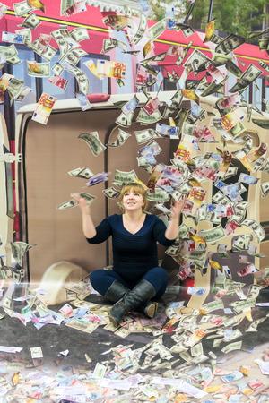 dinero volando: UFA - RUSIA 21 de febrero de 2016 - Una mujer posa para un efecto de ilusi�n �ptica de dinero volando a su alrededor en una demostraci�n p�blica gratuita en Ufa, Rusia durante febrero de 2016.