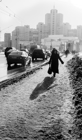 shoppingbag: Black and white image of an old woman with shopping bags walking on a busy snow covered foot path in a city as traffic and cars pass her.