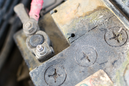 Closeup image of a corroded and defective car battery showing erosion of the terminals and residue build up