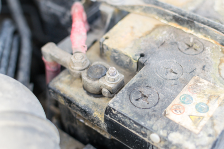 the residue: Closeup image of a corroded and defective car battery showing erosion of the terminals and residue build up