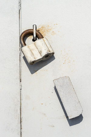 plating: Large industrial sized sealed padlock on grey paint and steel plating with copy space area