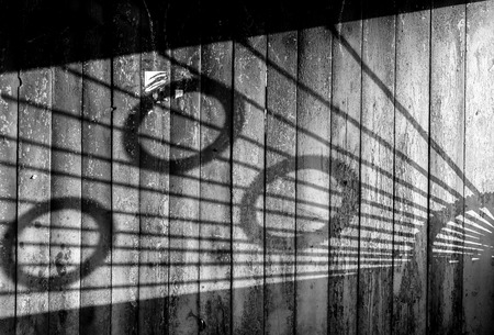 metal monochrome: Shadows from a metal patterned bus stop create a light abstract on the aged wood. Black and white monochrome image